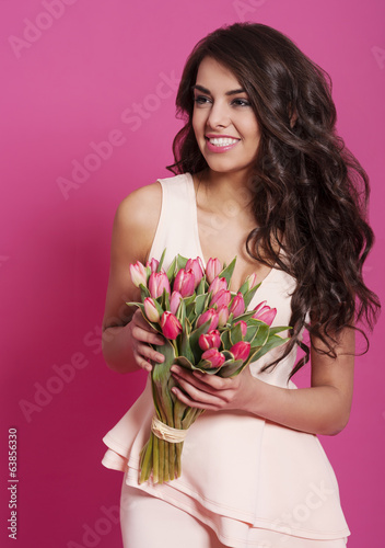 Happy young woman with pink tulips