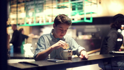 Young teenager adding sugar and mixing his coffee in cafe