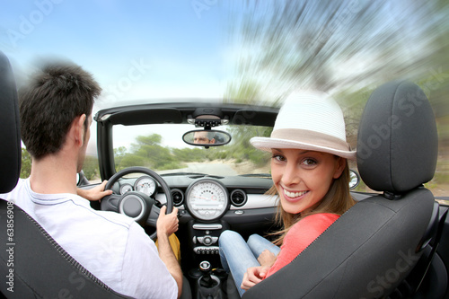 Young couple driving convertible car