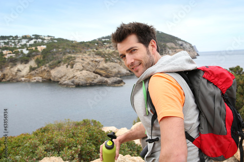 Portrait of hiker relaxing by the sea with bottle of water