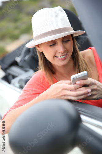 Trendy girl in convertible car using smartphone