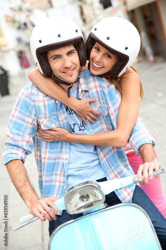 Portrait of couple riding vintage scooter