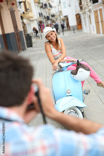 Man taking picture of girlfriend sitting on moto