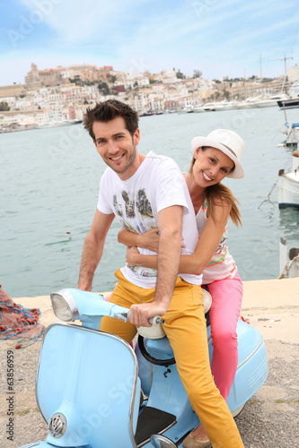 Cheerful couple riding vintage scooter in Ibiza