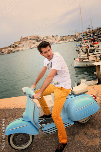 Stylish guy sitting on vintage moto in Ibiza