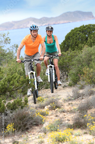 Couple riding bikes on island trail