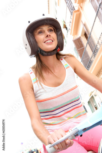 Portrait of young woman riding motorcycle in town