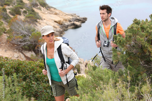 Couple of trekkers climbing island creek