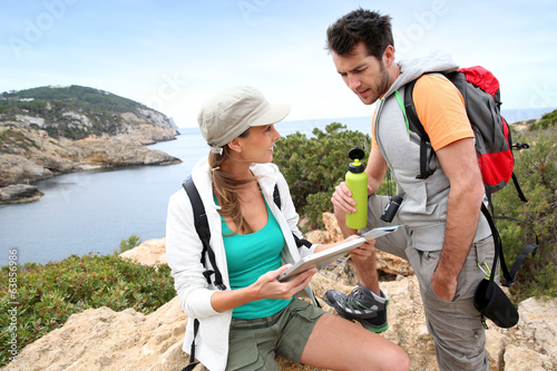 Couple of hikers reading map and using tablet