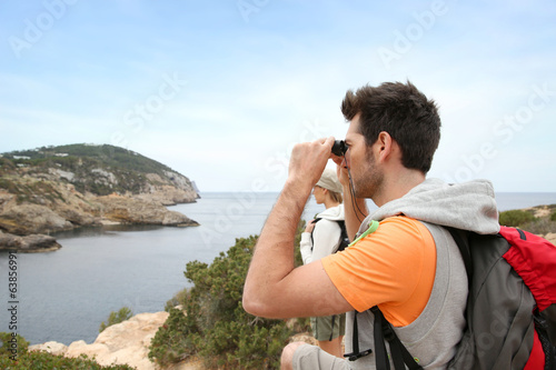 Man using binoculars on a hiking day