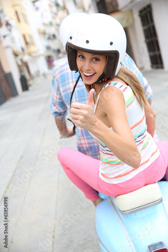 Girl riding moto with boyfriend and showing thumb up