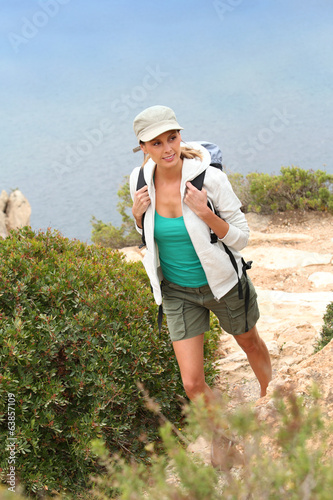 Young woman hiking by the sea on rocky pathway