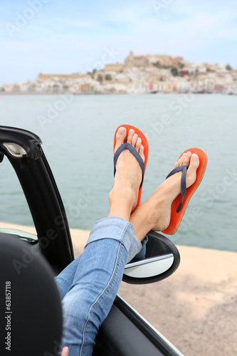 Closeup of woman's feet by convertible car window