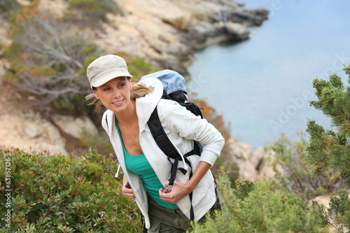 canvas print picture Young woman hiking by beautiful creek
