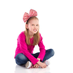 Little girl with hair bow sitting with legs crossed.
