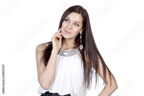 Cute young brunette with long hair thoughtfully dreams