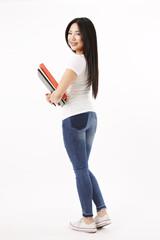 Studentin in weißen Shirt steht mit dem Rüchen zur Kamera