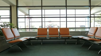 Seats at airport with airplane and cars in back