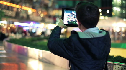 Young teenager filming city at night with tablet computer