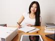 Studentin sitzt am Schreibtisch und schreibt