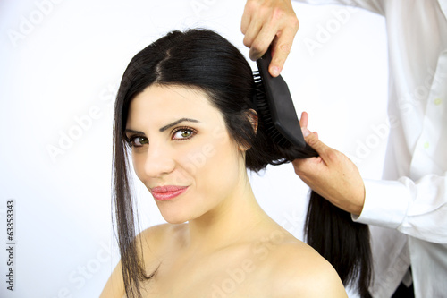 Beautiful woman getting hair brushed by stylist
