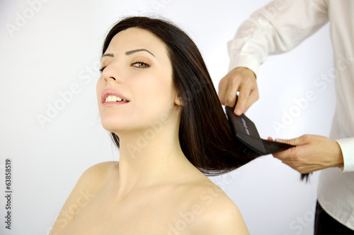 Happy woman getting long hair styled by professional coiffeur