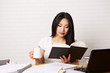 Studentin am Schreibtisch liest Buch 2
