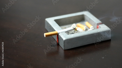 Hand smoke a cigarette in an ashtray