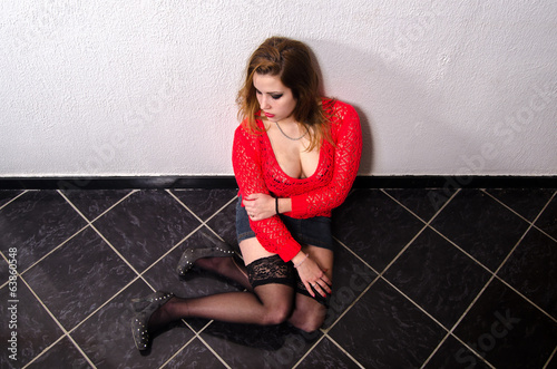 Victim of human trafficking  sitting on the floor