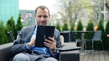 Young businessman with modern tablet computer sitting in cafe