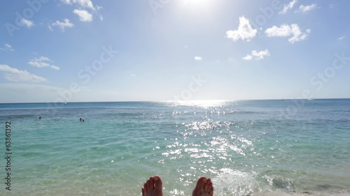 Feet relaxing by the ocean on a sunny day with clear blue sky
