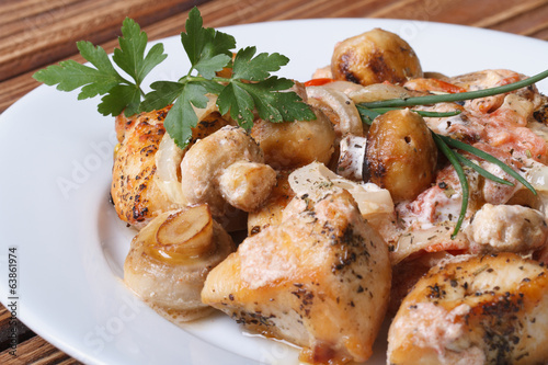 Sliced chicken with mushrooms and sauce on a white plate