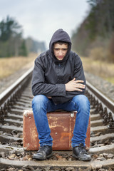 Teenage boy with a suitcase on the railway