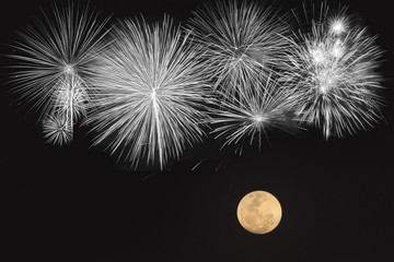 Fireworks and full moon  over black background