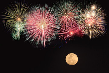 Colorful fireworks and full moon  over black background