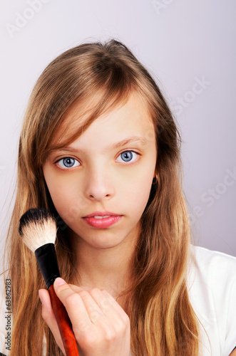 portrait of teenager girl doing makeup
