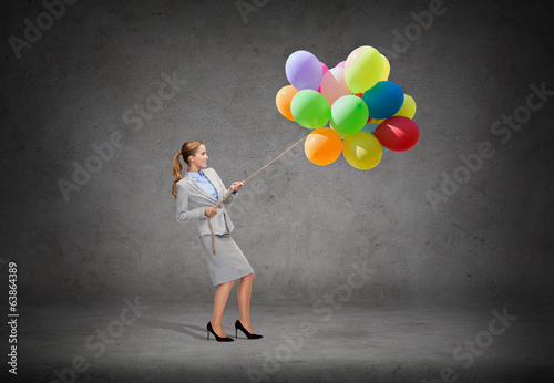 smiling businesswoman pulling rope with balloons