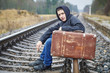 Teenage boy with a suitcase on the railway in rain