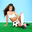 canvas print picture - Sexy busty tanned brunette with a soccer ball