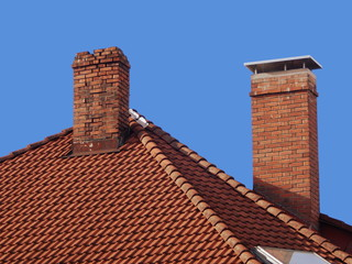 two brick chimneys on the roof, old and new