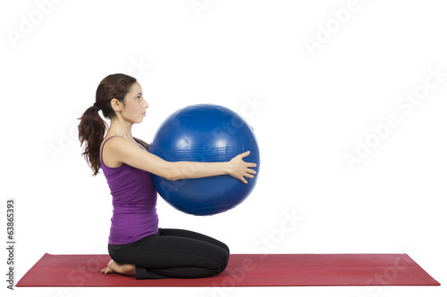 Fitness woman holding a pilates ball