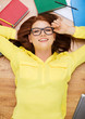 smiling student in eyeglasses lying on floor