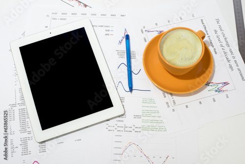 Tablet pc, cup of coffee and paper with graphs