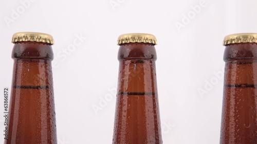 Conveyor Bottles of beer with drops isolated on white background