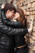 Happy young couple in love at the brick wall