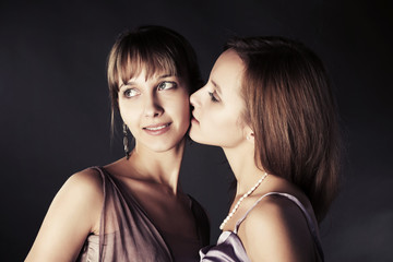 Two young beautiful women kissing