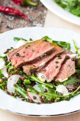 Salad with grilled beef steak, black lentils, rocket, radish