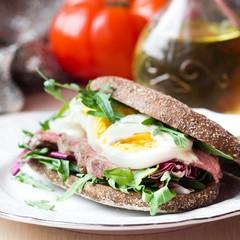 Sandwich with grilled beef steak, eggs, arugula, rye bread