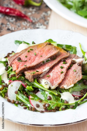 Salad with grilled beef steak, black lentils, rocket, radish