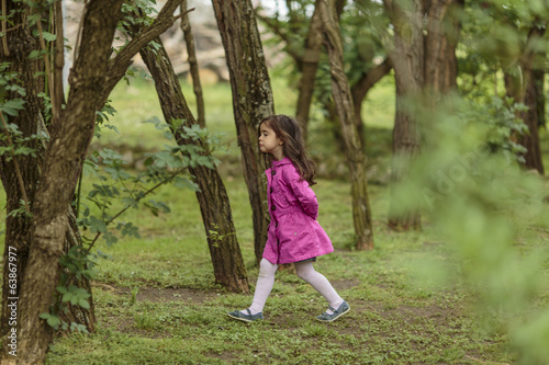 Little girl walking in the woods